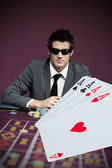 Gambler in sunglasses with digital four aces in foreground — Stock Photo