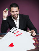 Handsome gambler betting on four aces — Stock Photo