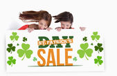 Girls holding placard with st patricks day sale text — Photo
