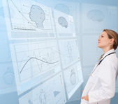 Thoughtful doctor looking at a medical new technology — Stock Photo