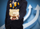 Businessman holding a piggy bank with international currencies — Stock Photo