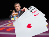 Gambler holding whiskey at poker table with digital hand of cards in foreground — Stock Photo