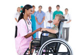 Nurse chatting with little boy in wheelchair — Stock Photo