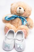 Teddy bear with blue ribbon and white booties — Stock Photo