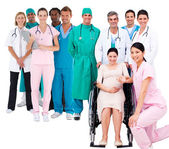 Nurse with pregnant woman in wheelchair with medical staff — Foto Stock