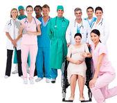 Verpleegster met zwangere vrouw in rolstoel met medisch personeel — Stockfoto