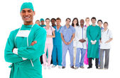 Lachende chirurg met medisch personeel achter hem — Stockfoto