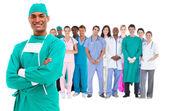 Uśmiechający się chirurg z personelem medycznym, za nim — Zdjęcie stockowe