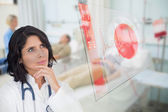 Doctor looking up at screen showing red ECG data — Stock Photo
