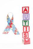 Autism awareness ribbon beside stacked blocks spelling autism — Stock Photo