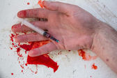 Lifeless hand holding bloody syringe — Stock Photo