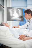 Doctor checking pulse of elderly patient beside screen displaying chest x-ray — Stock Photo