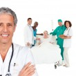 Smiling doctor with patient in bed and medical staff behind him — Stock Photo