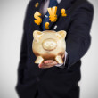 Businessman holding a gold piggy bank — Stock Photo #24060309
