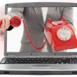 Woman reaching out from laptop handing phone receiver - Photo