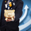Businessman holding a piggy bank with currencies — Stock Photo
