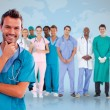 图库照片: Happy doctor with medical staff behind him