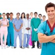 Smiling surgeon with medical staff behind him — Stockfoto