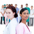 Serious doctor and nurse standing back to back — Stock Photo