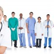 Smiling doctor standing in front of her medical team in line — Stock Photo