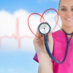 Happy nurse holding up stethoscope to heart design — Stock Photo #24061147