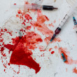 Three syringes lying on blood splatter — Stock Photo