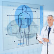 Senior doctor holding a clipboard beside display screens — Stock Photo