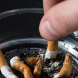 Hand putting out a cigarette in ashtray - Stock Photo