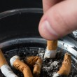 Hand putting out a cigarette in ashtray — Stock Photo #24061291