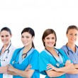 Smiling female hospital workers standing arms folded in line — Stock Photo
