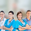 Female hospital workers standing arms folded - Foto Stock