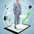 Smiling businessman standing on a tablet pc — Stockfoto