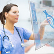 Nurse touching screen displaying blue DNA helix — Stock Photo