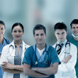 Smiling hospital workers standing arms crossed in line — Stock Photo #24062195