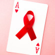 Red awareness ribbon lying on playing card - Stock Photo