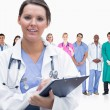 Woman doctor standing in front of her team in row — Stock Photo