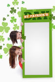 Girls holding blank green placard with patricks day text — 图库照片