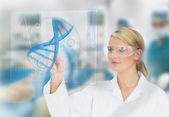 Doctor consulting touchscreen displaying DNA helix diagram — Foto Stock