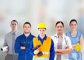 Smiling with different jobs standing arms folded in line — Stock Photo