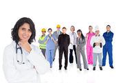 医生微笑着与她身后的各种工人 — 图库照片