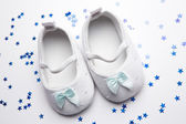 Baby blue booties with confetti — Stock Photo