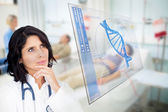 Doctor looking up at screen showing blue DNA helix data — Stock Photo