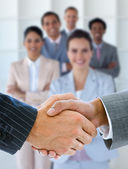 Businessmen shaking hands with team behind them — Stock Photo