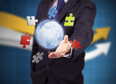 Businessman with colored puzzles and a globe — Stock Photo
