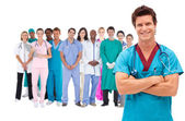 Smiling surgeon with medical staff behind him — Stock Photo