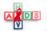 Blocchi di legno ortografia aids e hiv in una forma di croce con nastro rosso consapevolezza — Foto Stock