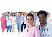 Smiling doctors in front of a team of doctors standing together — Stock Photo