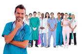 Happy surgeon with medical staff behind him — Stock Photo