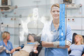 Smiling nurse standing behind blue display screen showing x-ray — Stock Photo