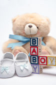 Blocks spelling baby boy with teddy and baby shoes — Stock Photo